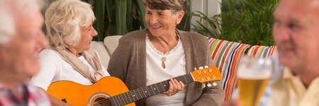 convivial: Two elder women sitting at the couch with one playing the guitar Stock Photo