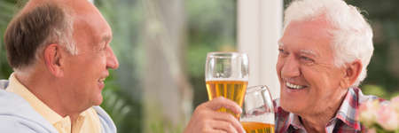 smiled: Closer shot of two elder men sitting face to face and drinking beer Stock Photo