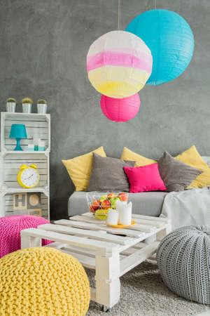 Beeld van een grijze woonkamer met kleurrijke poeven, hoofdkussens en lampschaduwen