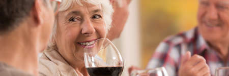 Closer shot of senior womans face with the glass of wine Stock Photo