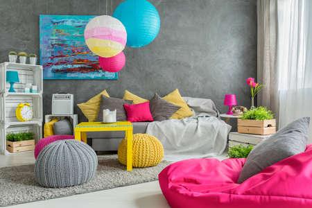 Gemütliches Wohnzimmer in grau mit Fenster, moderne Möbel und bunten Details Standard-Bild