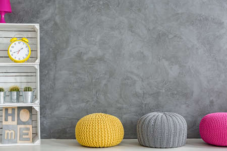 decorative wall: Grey home interior with DIY regale and three wool poufs Stock Photo