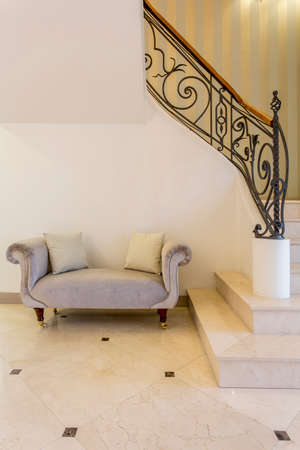 elegant staircase: Exclusive house- entrance with elegant sofa and marble staircase Stock Photo