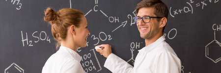 smiled: Smiled student explaining the chemical formula to his friend Stock Photo