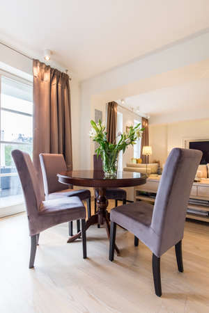 arrangements: Wooden round table in elegant living room interior