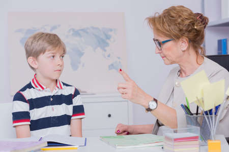 reprimand: Shot of a strict teacher pointing finger and giving a little student reprimand