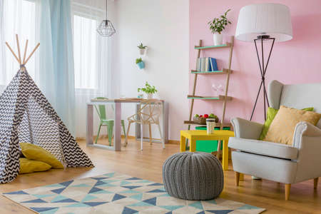 Spacious interior in pink and white with play tent, armchair, pouf, two chairs and table
