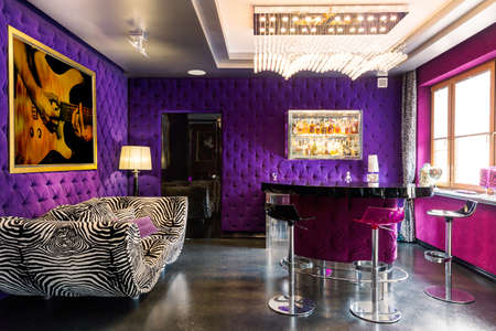 violeta: Bold violet and pink colours in the room with striped couch