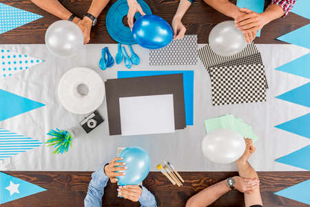 group shot: Shot of a group of friends sitting around a wooden table and preparing decorations for a party