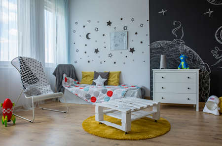 moon chair: Spacious child room in contemporary style with stars on the wall and blackboard wall