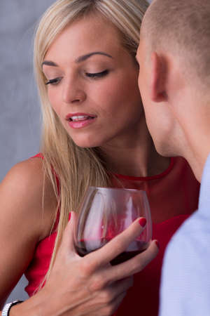 intrigue: Close shot of a man whispering on womans ear