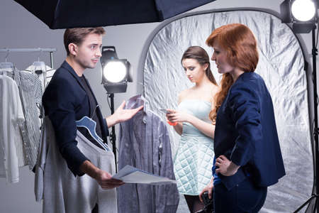 photo shoot: Shot of stylists choosing clothes for a model during a photo shoot
