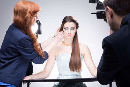 photo shoot: Shot of a make-up girl preparing a model for a photo shoot