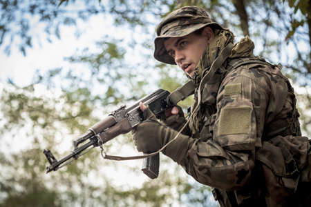 Image of a young soldier wearing military uniform pointing his gun Stock Photo