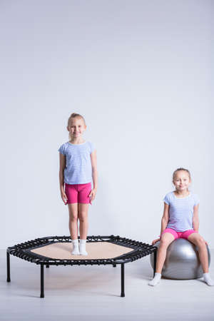 corrective: Shot of a girl standing on a trampoline and her friend sitting on a large exercise ball