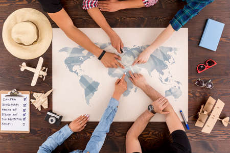 group shot: Shot of a group of friends pointing at a map laying on a table and planning their journey Stock Photo