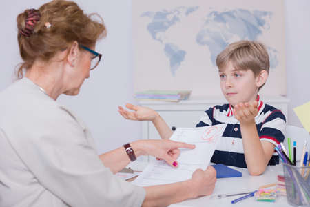 Shot of a tutor holding test with a F and a sad boy spreading his hands Stock Photo
