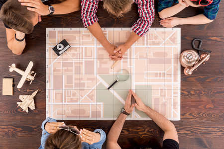 group shot: Shot of a group of friends sitting around a table with a city plan on it and planning their trip Stock Photo