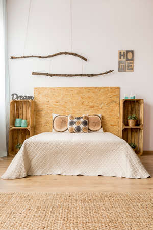 bedside tables: Light bedroom in ecological style with double bed, DIY bedside tables and carpet