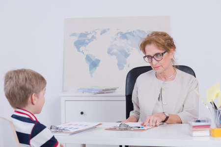 Shot of a principal with serious expression on her face, talking to a schoolboy