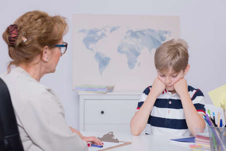 principal: Shot of a unhappy student sitting at a desk during a meeting with head teacher Stock Photo