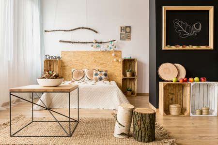 Lichte en ruime slaapkamer met zwart-witte muur en eco-doe-het-houten meubilair