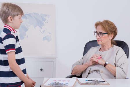 director de escuela: Tiro de una pequeña estudiante de pie junto a la directora que está sentado en un escritorio