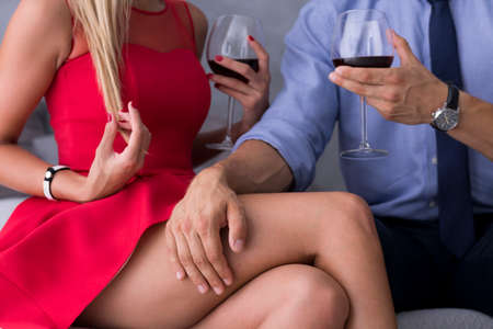 intrigue: Couple sitting close each other with the mans hand on womans tight