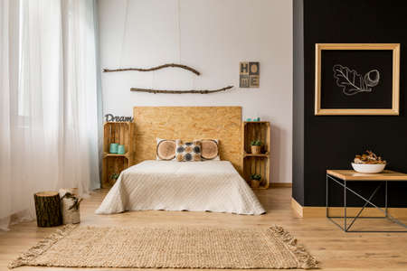 original ecological: Black and white bedroom with wooden DIY furniture and creative home decor Stock Photo