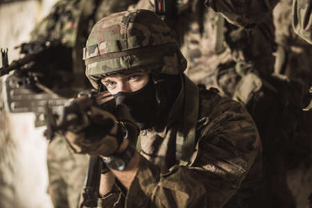 Young uniformed soldier with a gun ready to fire Stock Photo