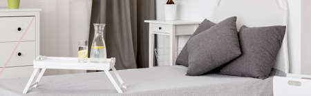 grey water: Bed for single with grey pillows and tray with a glass of water on it