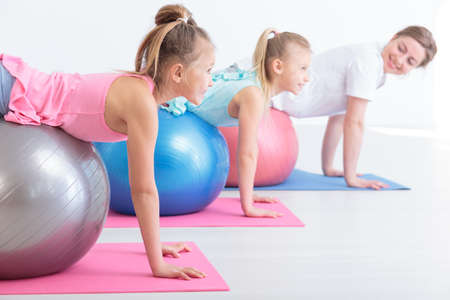color therapy: Cropped shot of two little girls and their physiotherapist during streching exercises Stock Photo