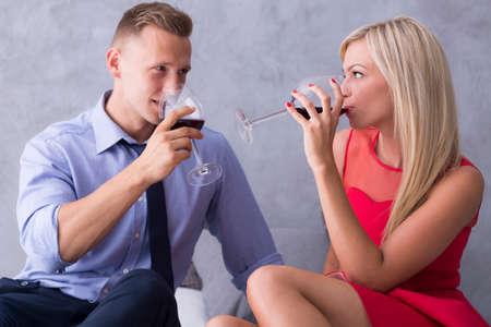 tomando vino: El hombre y la mujer sentada cerca entre sí y bebiendo vino Foto de archivo
