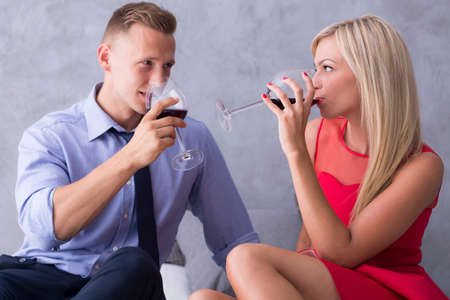 betray: Man and the woman sitting close each other and drinking wine Stock Photo