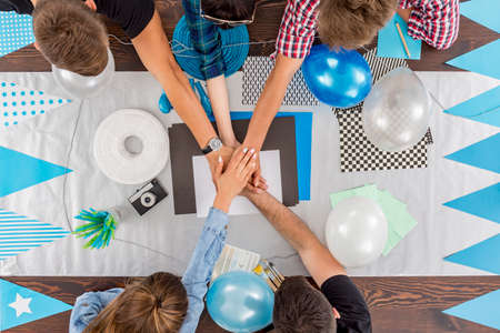 group shot: Shot of a group of friends preparing decorations for a surprise party Stock Photo