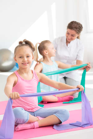 arm bands: Shot of two little girls doing band exercises with their physiotherapist in the background