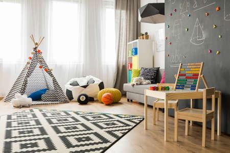 Ruime kinderkamer met raam, speeltent, zakstoel, patroontapijt, regale, sofa, kleine tafel, stoelen en schoolbordmuur