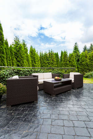 patio furniture: Wicker patio furniture with many plants in the backround