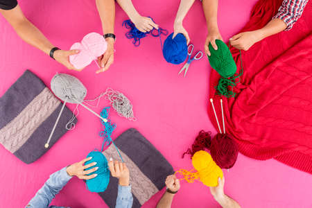 knitting: Shot of a group of friends holding colorful balls of wool