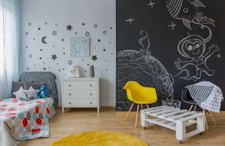 Cameretta luminosa con letto singolo, lavagna a muro decorata con stelle
