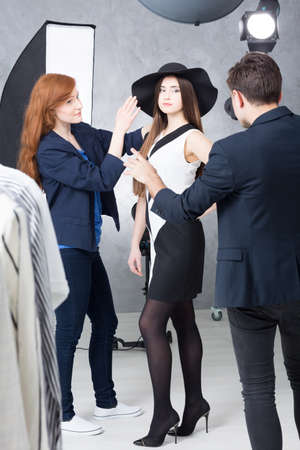 photo pictures: Shot of a stylist preparing a model for a photo shoot and a photographer taking pictures Stock Photo