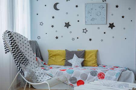 Cameretta luminosa con finestra, letto singolo e stelle sul muro