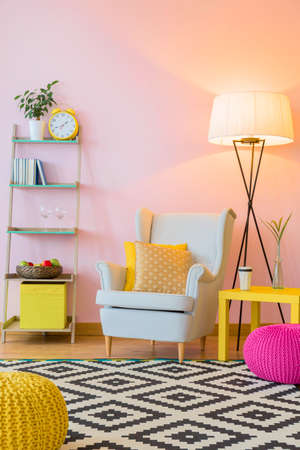 Cozy room in light pink with pattern carpet, comfortable armchair and floor lamp