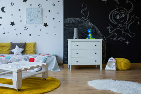 moon chair: Child room in contemporary style with blackboard wall, stars on the wall and simple furniture