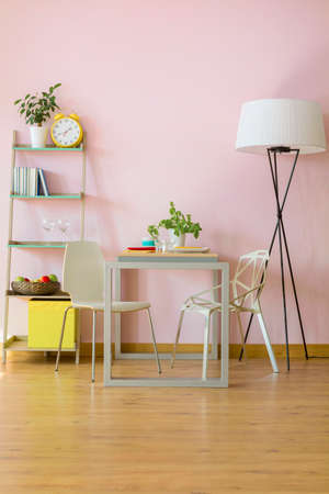 New style pink room with floor panels, table, two chairs, floor lamp and wall regale