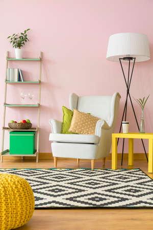 Gezellige kamer in lichtroze met comfortabele fauteuil en eenvoudige vloerlamp