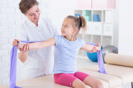 cropped shot: Cropped shot of a physiotherapist showing her patient how to hold her arms