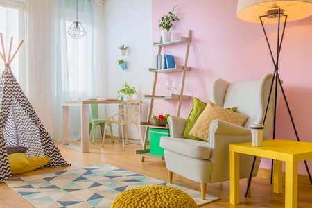 Ruime kamer in roze en wit met speeltent, gele tafel, fauteuil en eenvoudige vloerlamp
