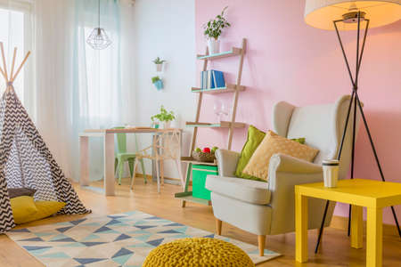 Spacious room in pink and white with play tent, yellow table, armchair, and simple floor lamp