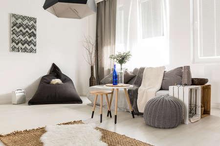Licht livng kamer met bean bag, comfortabele bank, doe-het-tafel, venster en stijlvolle decoratieve details